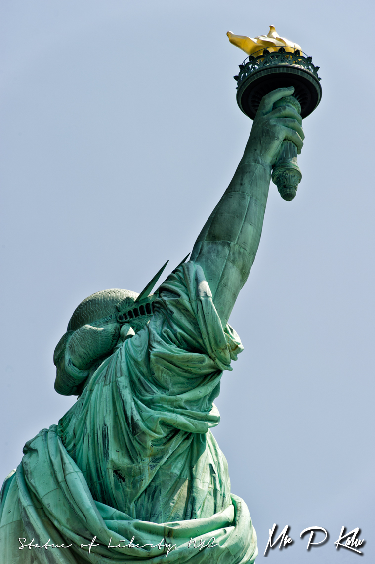 Statue-of-Liberty-upper-body-shot-with-torch-held-aloft-from-behind