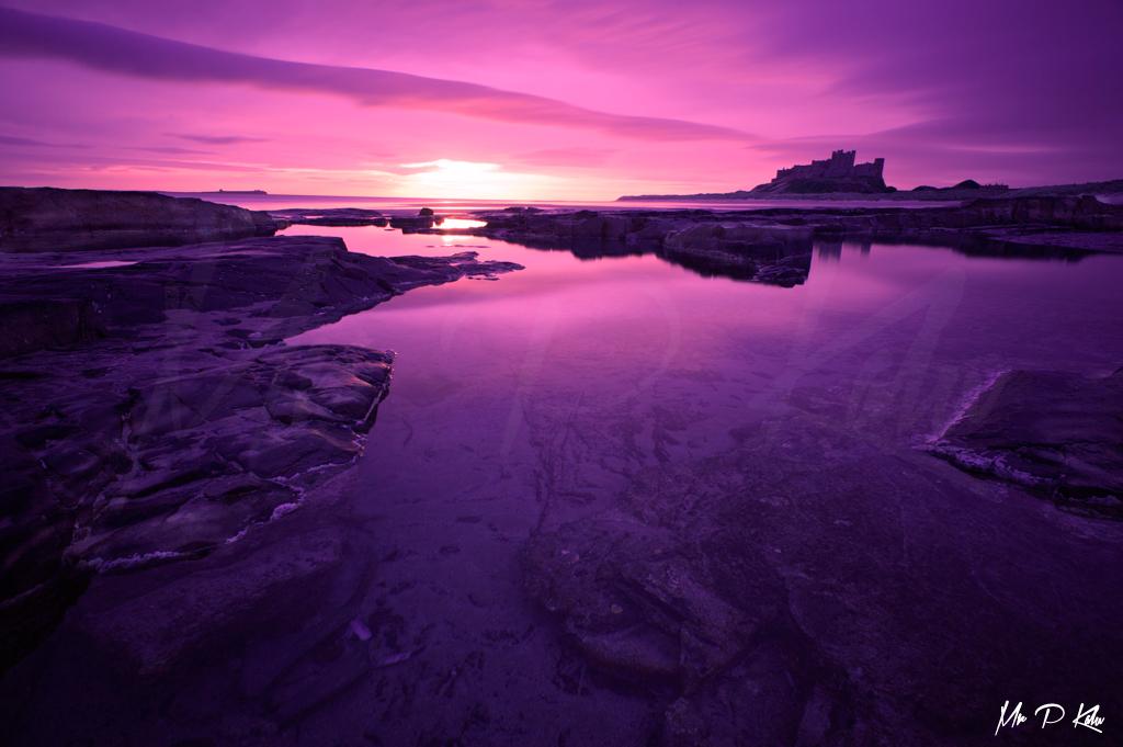 Bamburgh Castle Purple sky at sunrise on Bamburgh Beach Northumberland UK