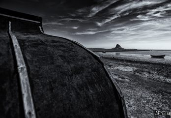 Black and white image of Lindisfarne Island Castle and an upside down Hewrring boat