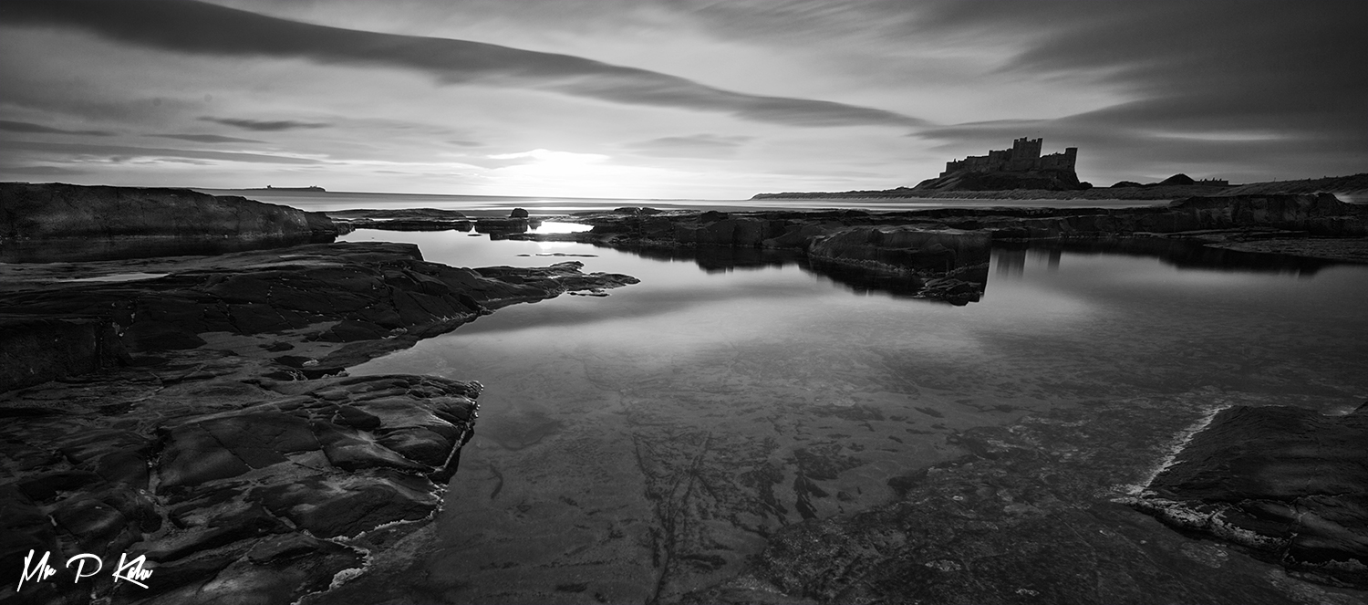 black and white image of bamburgh castle at sunrise by mrpkalu